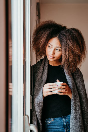 Thoughtful woman drinking coffee while looking through window at home