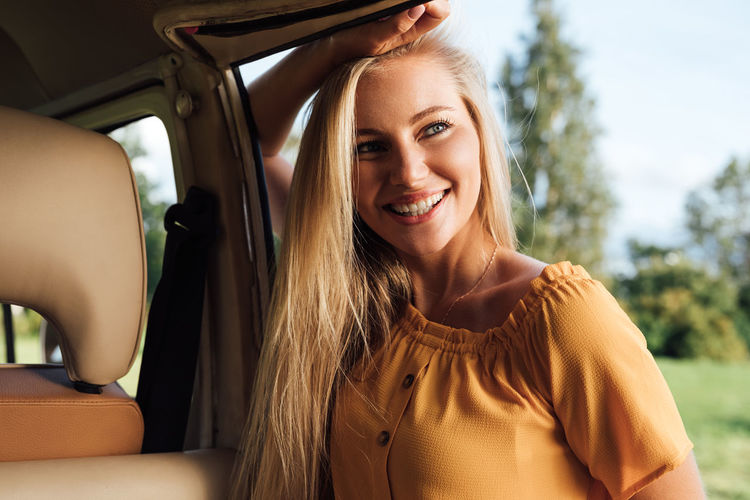 Portrait of smiling young woman sitting in car