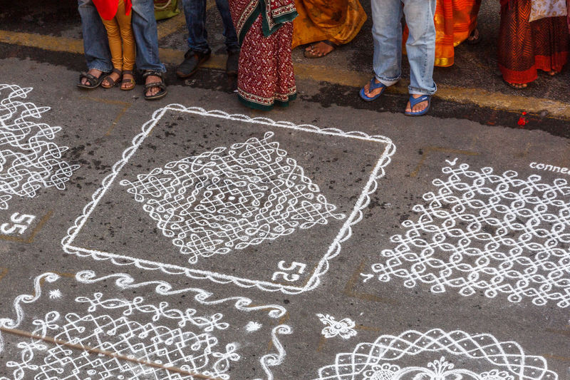 High angle view of people standing by rangolis on footpath during competition