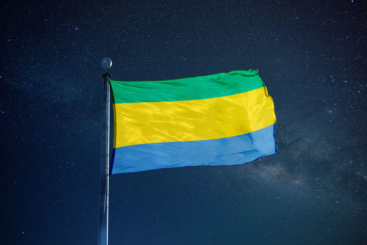 Low angle view of gabon flag against star field sky