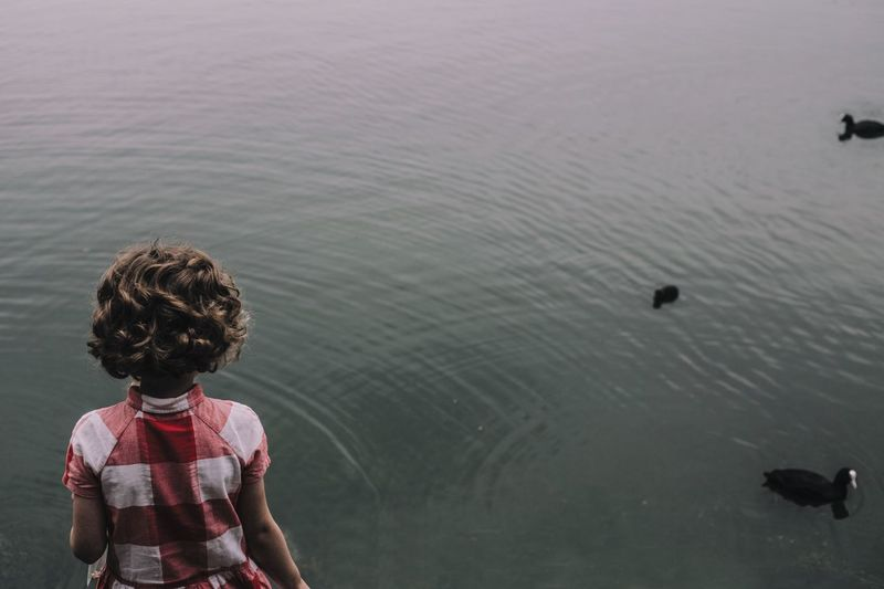 High angle view of girl standing by lake