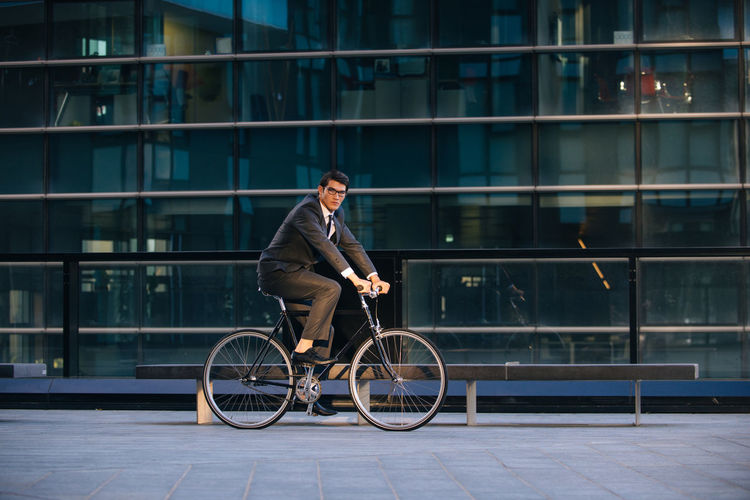 Man riding bicycle against building in city