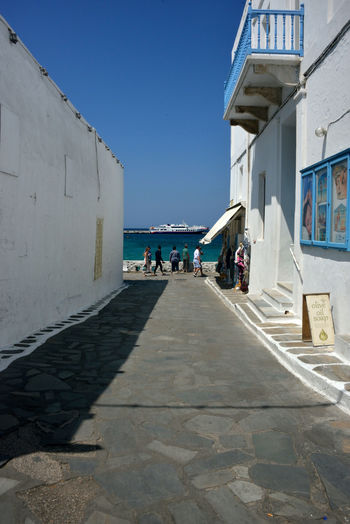 street view with white buildings and tourist walking near the sea Architecture Built Structure Building Exterior Group Of People Sunlight Sky Nature Day Clear Sky Real People Men Women Footpath Lifestyles Building Shadow People The Way Forward Direction Incidental People Outdoors Chora Mykonos,Greece Street View Cityscape Streetphotography Sea Greek Architecture Urban Travel Destinations White Building