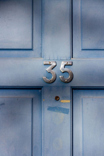 House number 35 on a light blue wooden front door in london