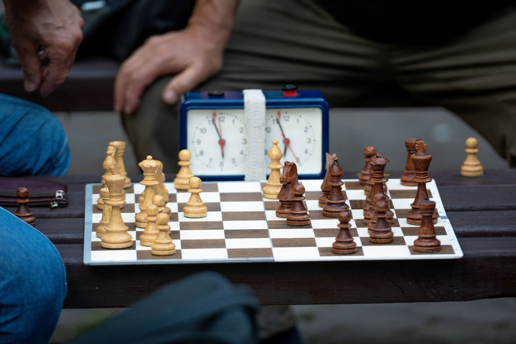 Midsection of men playing chess by clock on table