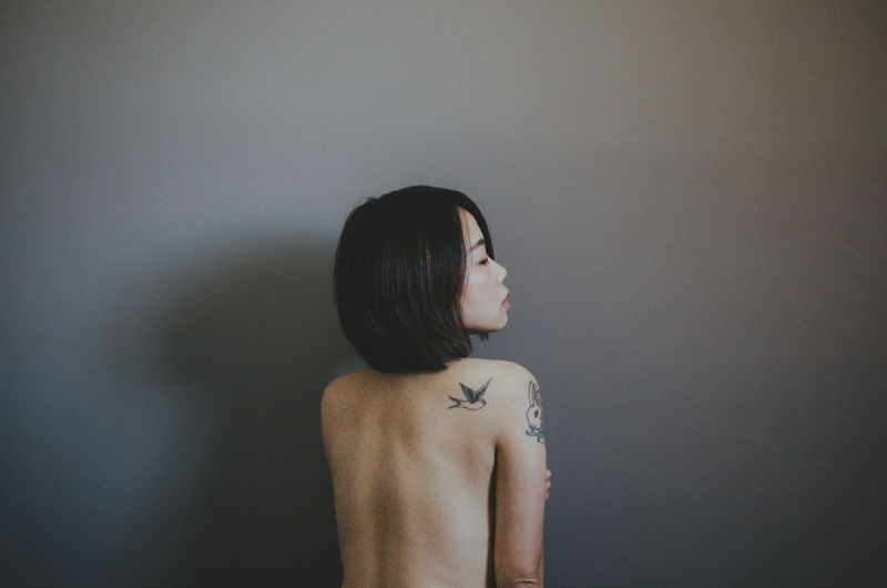 Rear view of shirtless woman standing against grey wall