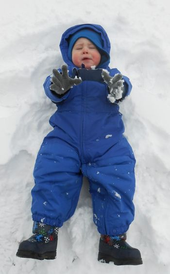 High Angle View Of Boy Lying On Snow Covered Field