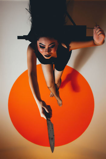 High angle view of young woman holding knife on floor