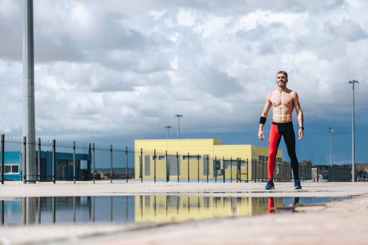 Shirtless Man Standing By Puddle On Street Against Cloudy Sky