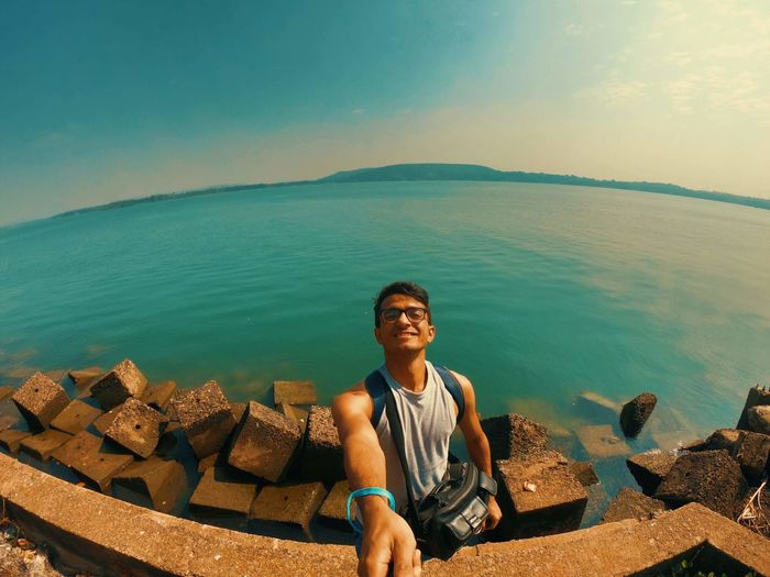 Portrait of young man sitting by sea against sky