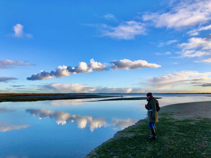 Man standing in lake against sky