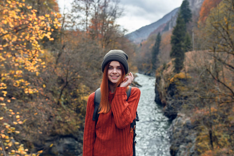 Portrait of a smiling young woman standing during autumn