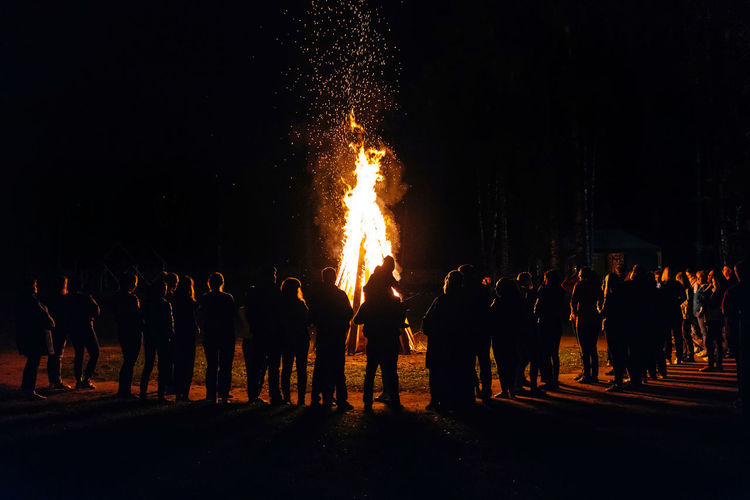 People standing against bonfire