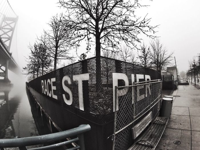 Tree Architecture Built Structure No People Building Exterior Communication Text Outdoors Land Vehicle Day Bare Tree Sky Metal Fences And Beyond Fences RaceStreetPier Philly Phillylove ❤️ Blackandwhite Photography Highcontrast Winter Wintertrees Wet Day Wetweather Citylife
