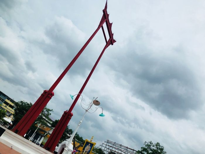 Low angle view of crane against sky in city