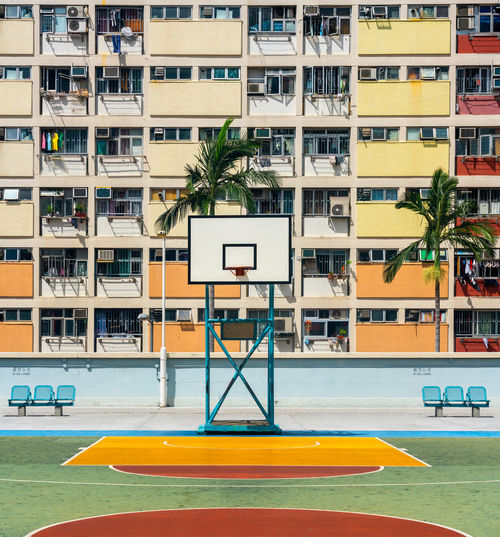 Basketball hoop on sports court against building in city