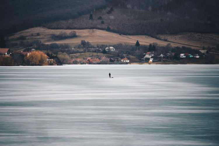 Distant view of person standing on frozen lake