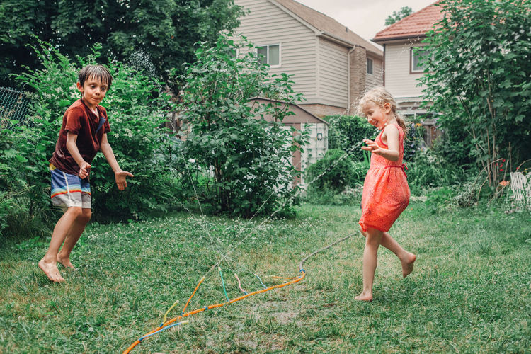 Siblings playing with sprinkler at yard