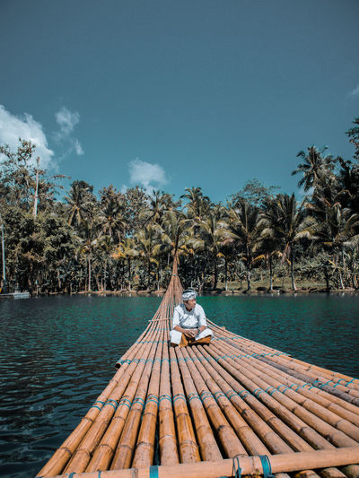 Man sitting on wooden raft over lake against trees