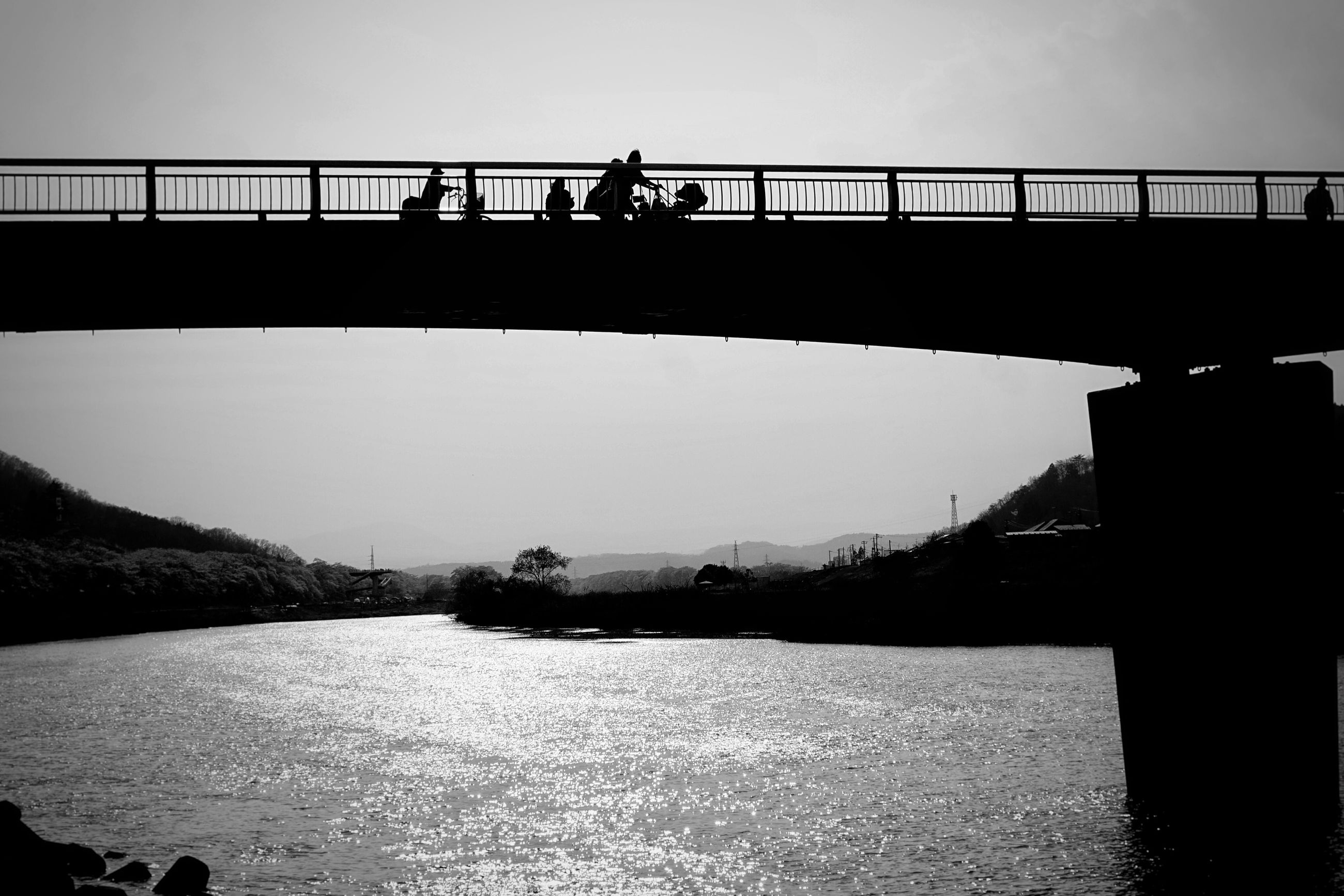 bridge - man made structure, connection, bridge, built structure, architecture, railing, river, sky, outdoors, real people, silhouette, men, clear sky, lifestyles, day, water, travel destinations, footbridge, city, mountain, nature, people