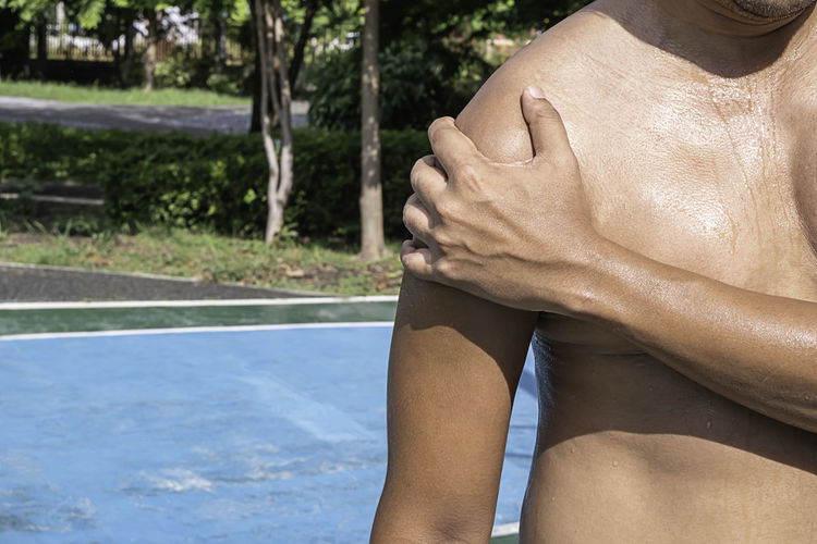 Midsection of shirtless man in swimming pool