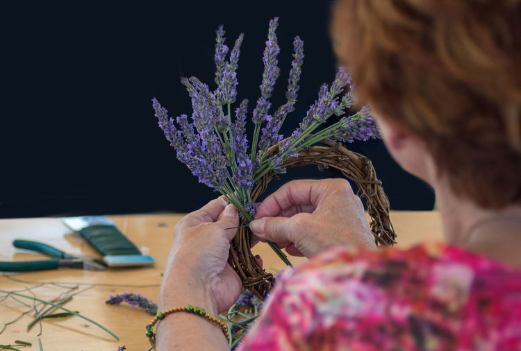 Cropped image of woman making a wreath with fresh lavender