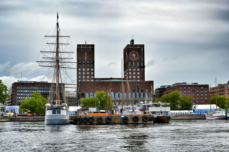 Boats moored on river by city against cloudy sky
