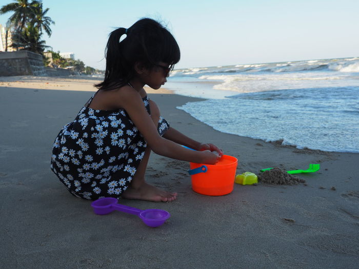 Rear view of girl with toy on beach