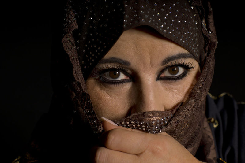 Close-Up Portrait Of Woman With Face Wrapped In Scarf Over Black Background