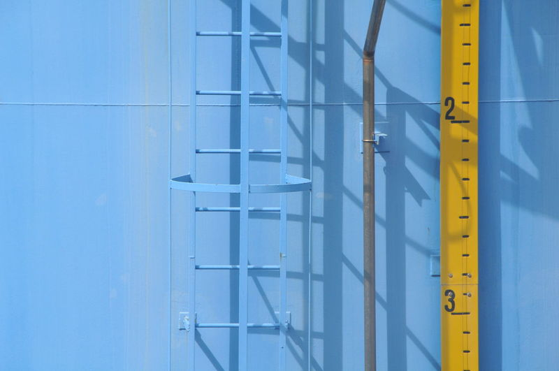 Ladder and measure tape on container