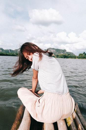 Portrait of woman sitting on wooden raft over lake against sky