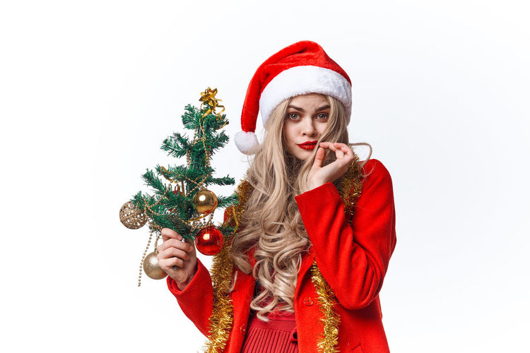 Young woman with umbrella on christmas tree against white background