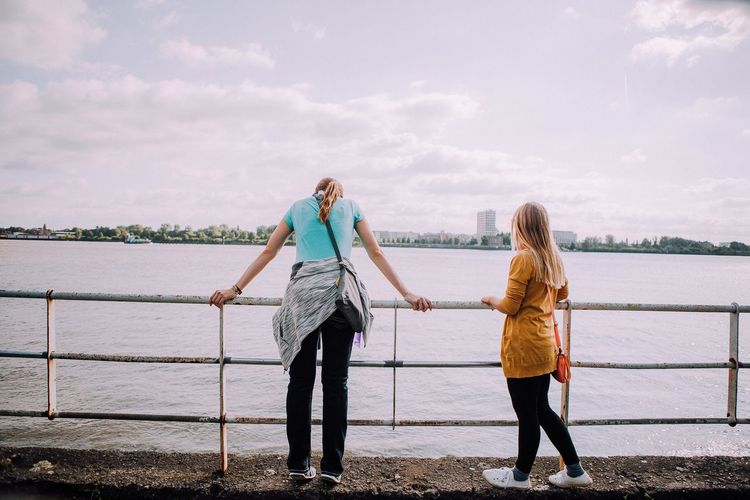 Female Friends Standing By River Against Sky