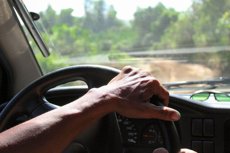 Cropped hand of person driving car outdoors