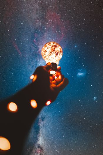 Cropped hand holding illuminated light bulb against sky at night