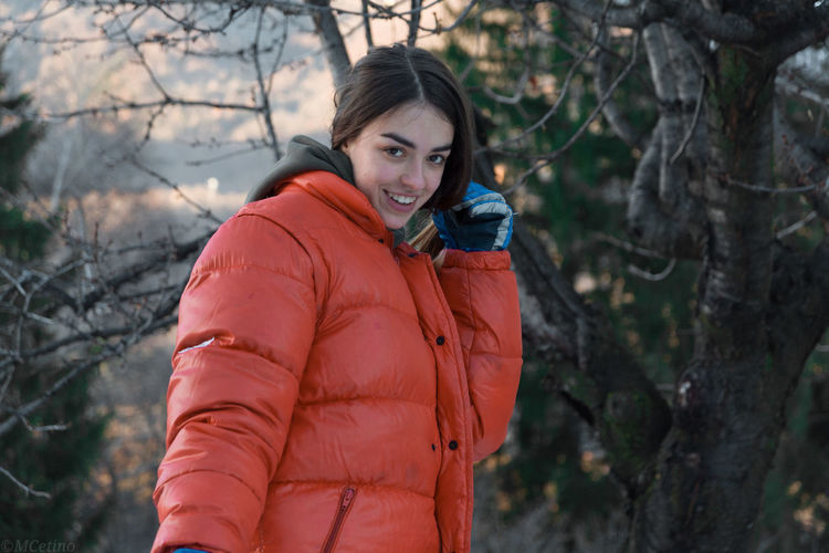 Portrait of smiling young woman standing by tree during winter