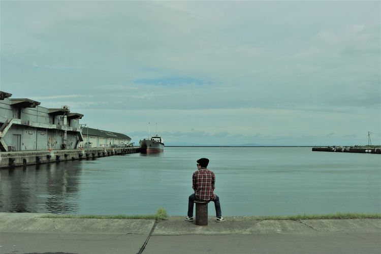 Rear view of teenage boy looking at sea while sitting on bollard against cloudy sky