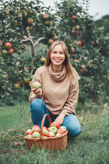 Portrait of smiling young woman holding apple while crouching by basket against trees