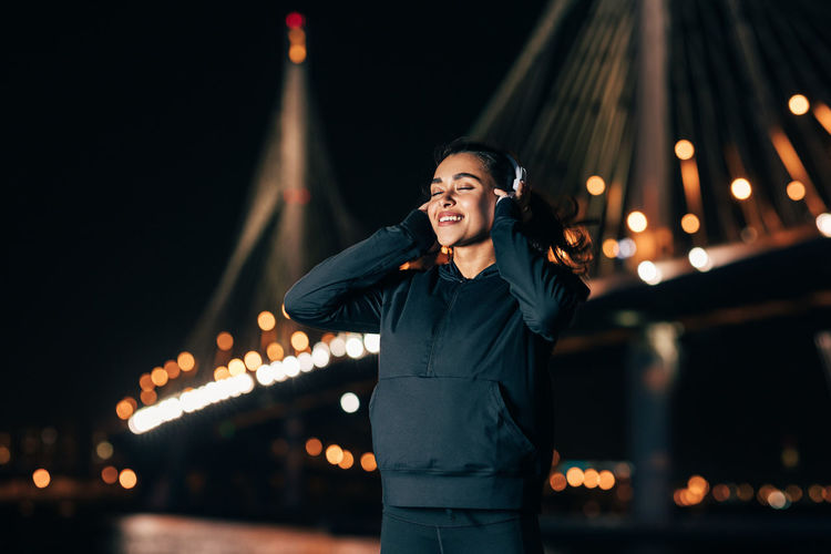 Smiling young woman standing against illuminated city at night