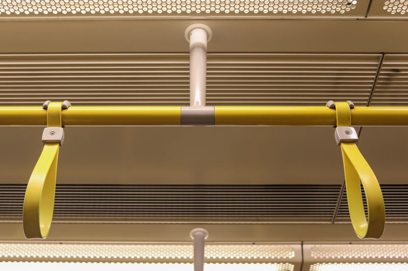Close-up of yellow metal railing against wall