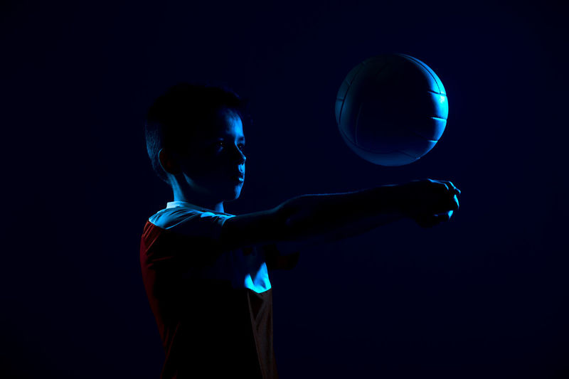 Boy playing with volleyball in darkroom