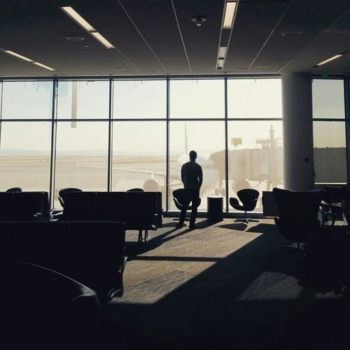 Rear view of man standing in waiting area of airport