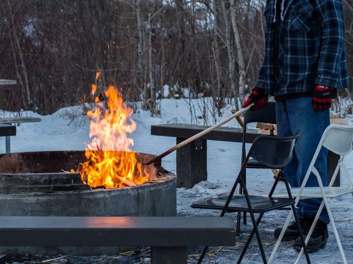 Man standing with stick by fire during winter