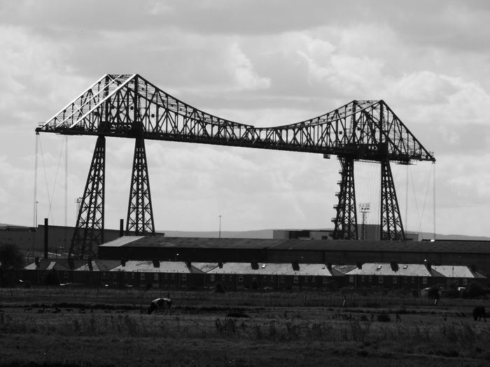 Tees transporter bridge by field against sky at middlesbrough