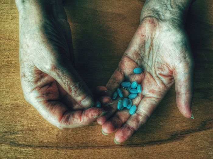 Close-up of hands holding pills