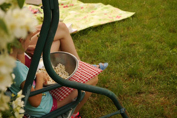 Girl Having Popcorn While Siting On Bench In Yard