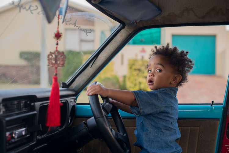 Ride with me African Auto Portrait Car Child Childhood Children Only Curly Hair Cute Day Domestic Life Driving Fun One Boy Only One Person Outdoors People Smiling Steering Wheel Vehicle Interior Market Bestsellers 2017