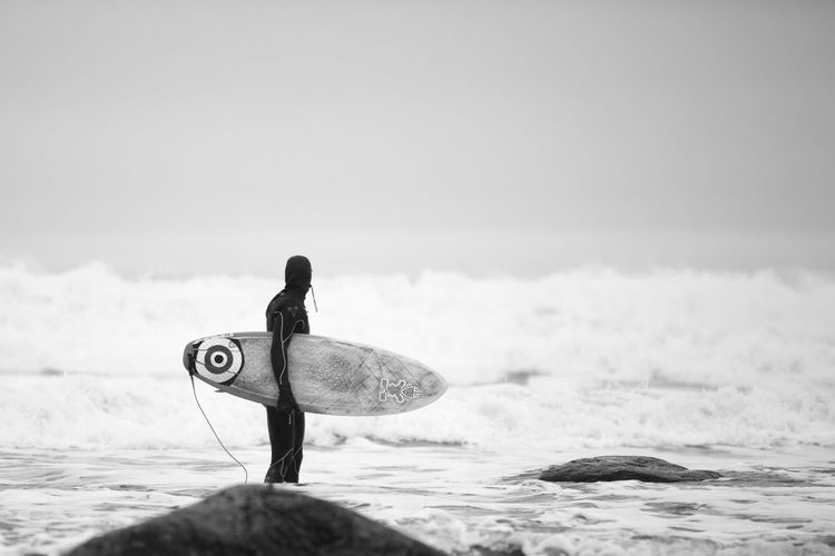 Man With Surfboard Standing At Sea Shore Against Sky