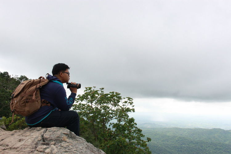 Side view of man with video camera sitting on cliff against cloudy sky