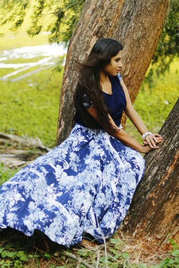 Young woman wearing gown while sitting on tree trunk